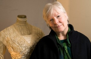 <p>Laura Crow, professor of dramatic arts, with a costume from the University's historical collection. Photo by Frank Dahlmeyer </p>