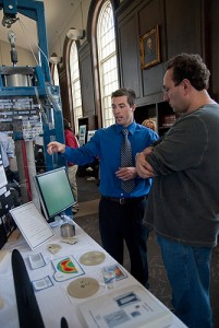 <p>Mechanical engineering major Brian Beahn explains his senior design project to a visitar at gather at Wilbur Cross Library's senior design project convention on April 30, 2010. Photo by Lauren Cunningham</p>