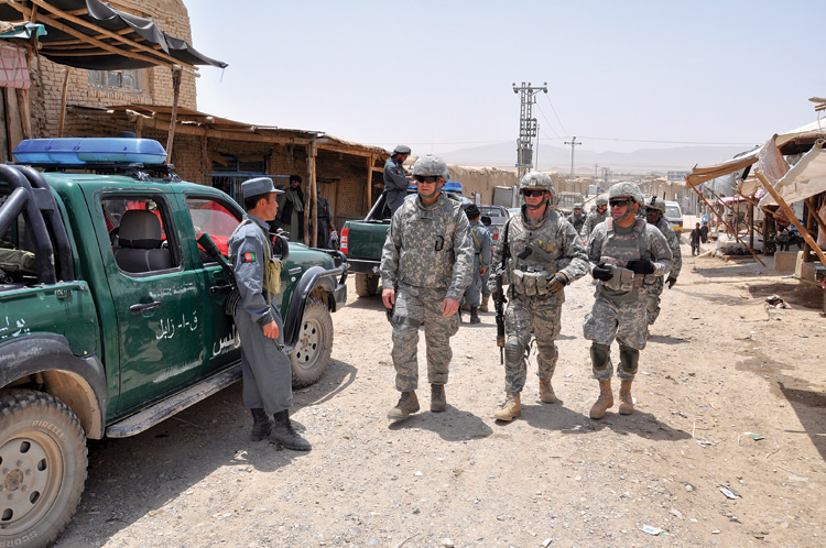 Col. Erik Goepner, '89 (CLAS), center, commander of the Zabul Provincial Reconstruction Team, accompanies other military personnel during a visit to local merchants in Qalat, Zabul province, Afghanistan.