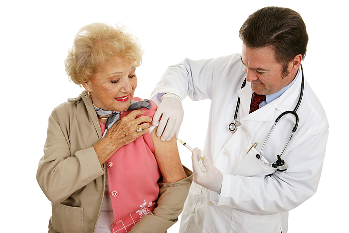 Senior woman receiving a flu shot from her doctor. (Stock photo)