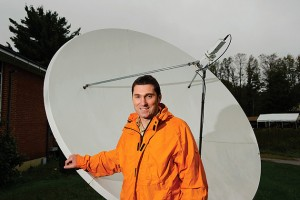 Emmanouil Anagnostou, professor of civil and environmental engineering,  stands near a satellite receiving dish. (Peter Morenus/UConn Photo)