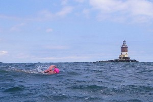 Elizabeth Fry swims past Romer Shoal Light on the outbound leg of her round-trip Ederle Swim from Manhattan to Sandy Hook, N.J. last June. (Vladimir Brezina photo)
