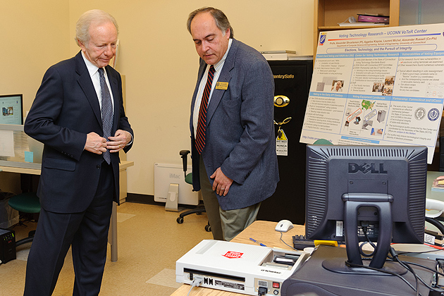 Alexander Shvartsman, professor of computer science and engineering, shows Sen. Lieberman an example of an electronic voting device at the Center for Voting Technology Research. (Peter Morenus/UConn Photo)