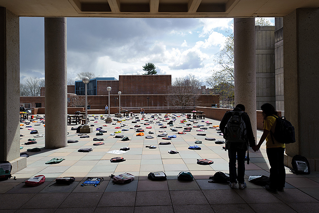 A pair of students outside the Homer Babbidge Library view the 1,100 backpacks, many of which were accompanied by personal stories of those lost to suicide. (Peter Morenus/UConn Photo)