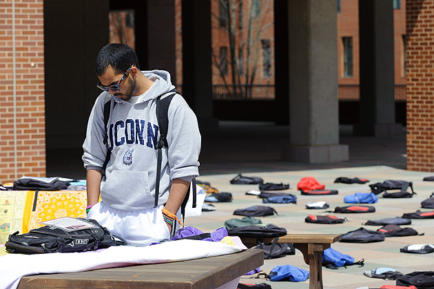 David Vidaurre '14 (CLAS) looks at a note attached to one of 1,100 backpacks, representing the number of college students who die by suicide each year cover the Homer Babbidge Library Plaza on April 12, 2012. (Peter Morenus/UConn Photo)