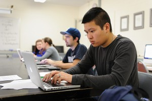 Eric Vo '13 (CLAS) works on his reporting project. (Peter Morenus/UConn Photo)