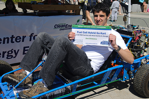 Neil Spinner, a Ph.D. student in chemical engineering, poses with his fuel cell go-kart. (Max Sinton '15 (CANR)/UConn Photo)
