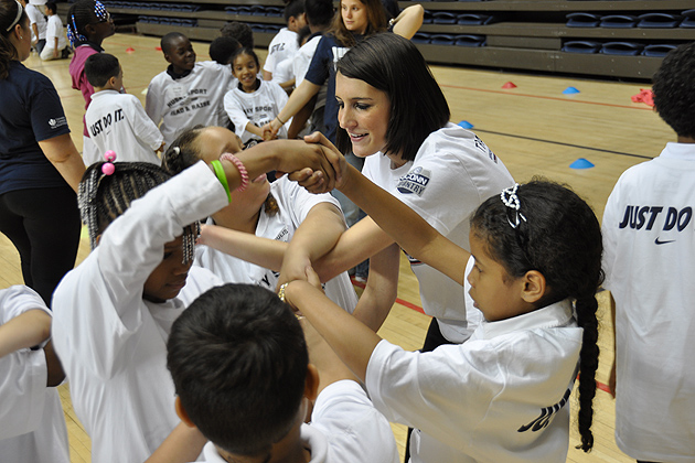 """UConn student Alex Badalucco leads a """"knot"""" activity involving team building skills, during the Read & Raise recognition event April 23. (Shawn Kornegay/UConn Photo)"""