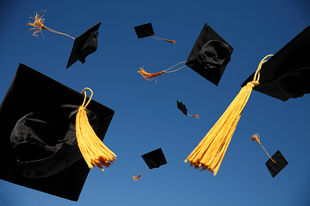 Group of mortar board caps being thrown in the air.
