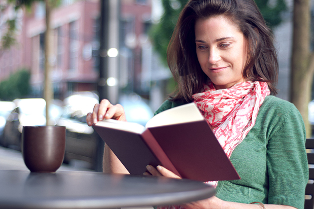 Woman reading book with cup of coffee.