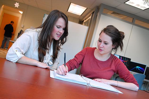 Kayla Everson '12, left, tutors Sarah Adams '12 in the Academic Achievement Center on Dec. 14, 2011. (Ariel Dowski/UConn Photo)