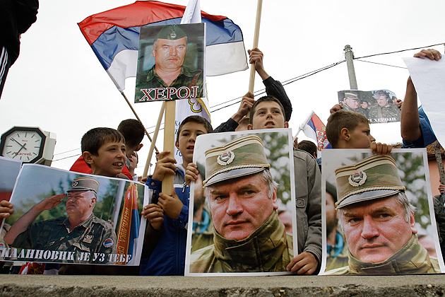 Bosnian Serb people holding Serbian flags and photos of former Gen. Ratko Mladic after the arrest of the Bosnian Serb wartime military leader. Mladic was put on trial at the International Criminal Tribunal in the Hague for war crimes and crimes against humanity, including genocide in Srebrenica in 1995. (AP Photo/Amel Emric)