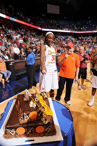 The Connecticut Sun and the team's fans sent former Huskies Tina Charles '10 (CLAS) and Asjha Jones '02 (BUS) off to the 2011 London Olympic Games with a chocolate cake decorated with basketballs .Charles is just about to cut the cake in this photo. (Copyright 2012 NBAE Photo by Brian Babineau/NBAE via Getty Images)