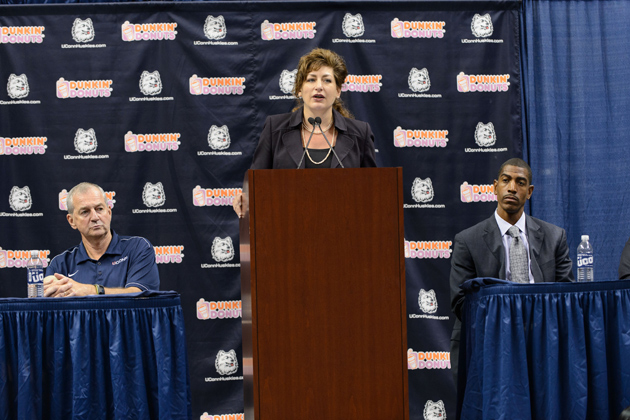 President Susan Herbst, center, speaks at a press conference in Gampel Pavilion to announce the retirement of Jim Calhoun, left, and the appointment of Kevin Ollie, right, as head men's basketball coach on Sept. 13. (Peter Morenus/UConn Photo)