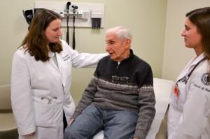 Dr. Karen Hook (left) with a patient, observed by medical student Nicole Albino. (Chris DeFrancesco/UConn Health Center Photo)