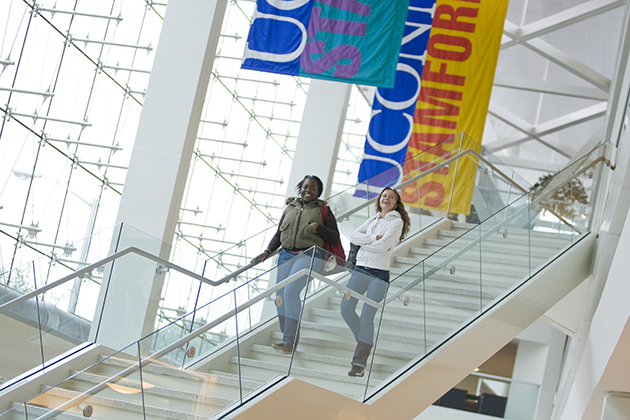 Photo of a students walking down the main stairwell at the Stamford Campus with banners in the background.(Peter Morenus/UConn)