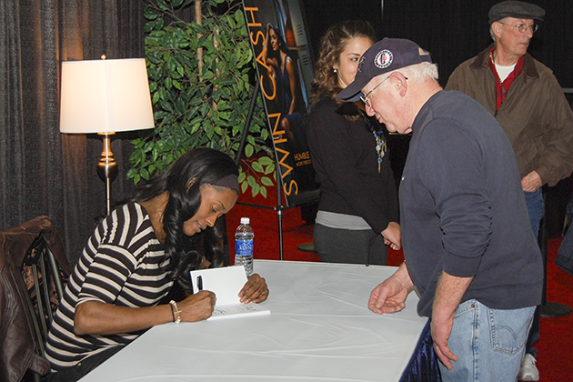 Swin Cash '02 (CLAS) signs copies of her book at the XL Center during the Big East Women's Basketball Tournament. (Ken Best/UConn Photo)