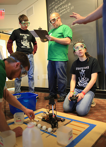 Students from Hopkins School in New Haven get ready to test their robot arm machine. (Michael Fiedler for UConn)