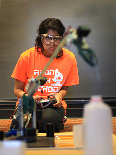 Aneesha Ramen of Avon High School directs her team's robot arm to drop a nail into a milk container. (Michael Fiedler for UConn)