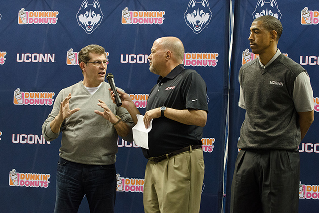 Joe D'Ambrosio, center, interviews coaches Geno Auriemma, left, and Kevin Ollie during a ceremony to unveil new athletic uniforms at Gampel Pavilion on April 18, 2013. (Peter Morenus/UConn Photo)