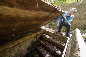 Stuart Miller, professor of hebrew, history and Judaic studies points to the spot at which water would enter a former mikvah in Old Chesterfield.. (Peter Morenus/UConn Photo)