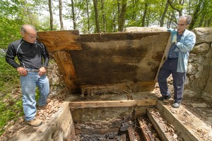 Nicholas Bellantoni, state archeologist, left, Stuart Miller, professor of hebrew, history and Judaic studies look down into the site of a former mikvah. (Peter Morenus/UConn Photo)