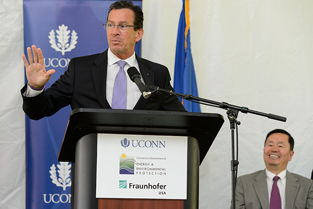 Governor Dannel P. Malloy speaks at an event held at the University of Connecticut Depot Campus to mark the Inauguration of the Fraunhofer Center for Energy Innovation (CEI) at UConn on July 25, 2013. Seated at right is Provost Mun Choi. (Peter Morenus/UConn Photo)