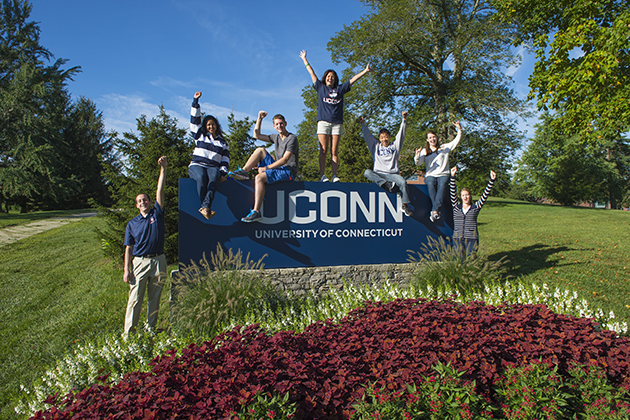 Students cheer while standing with the University sign near the corner of North Eagleville and RT 195 on Sept. 6, 2013. (Peter Morenus/UConn Photo)