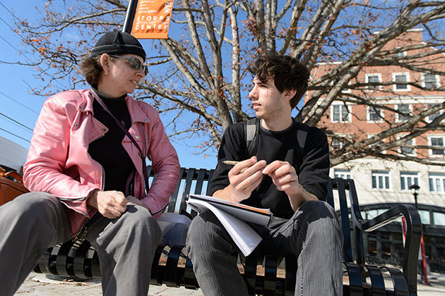 Cora Lynn Deibler, professor of fine art, talks with Bruno Perosino '17 (SFA) about his sketches while seated on a bench at Storrs Center on Oct. 28, 2013. (Peter Morenus/UConn Photo)