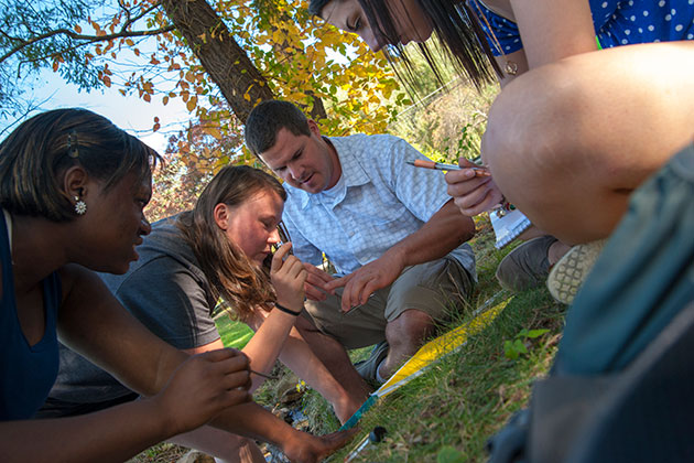 From left, Tiffany Cousins '14, Kamilla Dynia '14, Kevin Evringham (teaching assistant), and Victoria Chilinski '16, look over water samples taken during an outdoor geography class introducing environmental processes and patterns, especially assessing change in environmental systems using spatial analysis techniques. (Sean Flynn/UConn Photo)