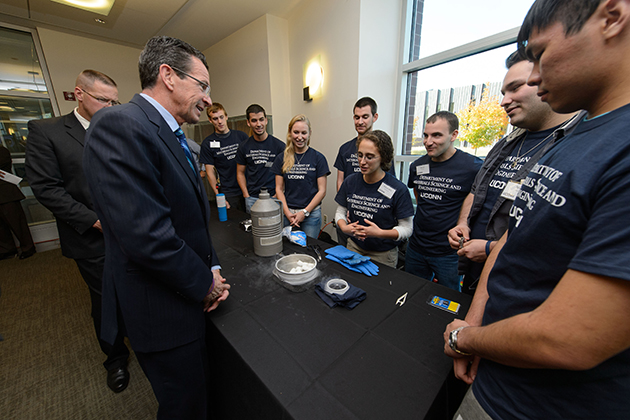 Institute of Materials Sciences students show a superconductivity experiment to Governor Dannel P. Malloy following a ceremony to commemorate the final approval of Next Generation Connecticut legislation held at the Information Technologies Engineering Building on Oct. 21, 2013. (Peter Morenus/UConn Photo)