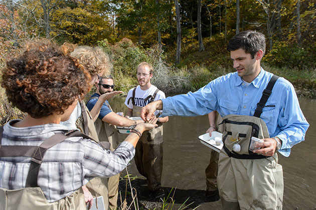 Mark Urban, right, assistant professor of ecology & evolutionary biology leads a limnology class at the Fenton River swamp on Oct. 3, 2013. (Peter Morenus/UConn Photo)
