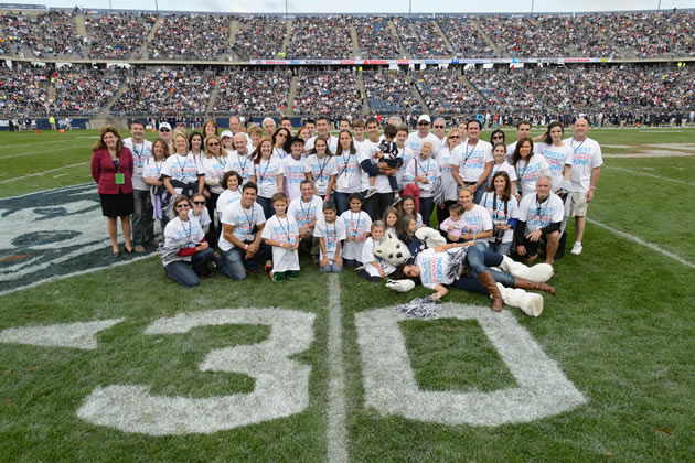 """Members of the Stamos/Heerdt/Vartelas/Vlandis family pose for UConn's """"Biggest UConn Family"""" portrait at Rentschler Field on Saturday, Oct. 12, 2013. Almost 60 family members received an exclusive Homecoming package, including tickets to the game, admission to the Alumni Association BBQ, T-shirts, and on-field recognition. (Peter Morenus/UConn Photo)"""