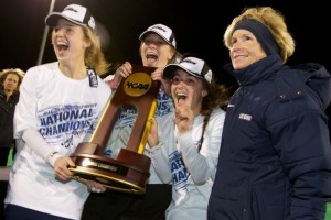 From left, forward Anne Jeute '14 (CLAS), goaltender Sarah Mansfield '14 (CLAS), forward Marie Elena Bolles '14 (NUR), and head coach Nancy Stevens, with the 2013 NCAA Championship trophy. (Keith Lucas for UConn)