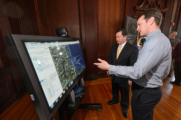 Todd Fake, right, a researcher at the UConn Marine Sciences Technology Center, left, explains a tool for predicting storm surge to Provost Mun Choi during and event to announce the launch of the Institute for Community Resiliency and Climate Adaptation held on Jan. 24, 2014 at the Branford House at the University of Connecticut Avery Point campus in Groton. (Peter Morenus/UConn Photo)