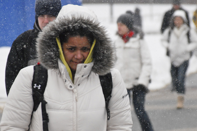 Students bundle up to keep warm while walking to classes on a snowy, winter day.