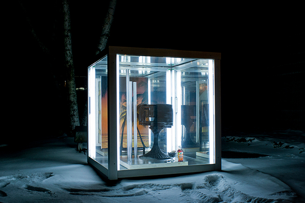 'Paradise Sale,' a work by Martin Basher of New Zealand, is a mixed media work that includes Plexiglas, aluminum, and fluorescent lights on a concrete base. Located outdoors, at night it reveals a painting of a sunset beach. (Photo by Contemporary Art Galleries)