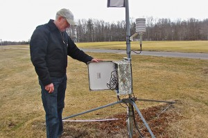 Olsen looks at the weather monitoring device that records temperature every 15 seconds. (Sheila Foran/UConn Photo)