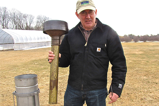 Steve Olsen '85 (CANR) lifts the internal precipitation measuring device out of its container. (Sheila Foran/UConn Photo)
