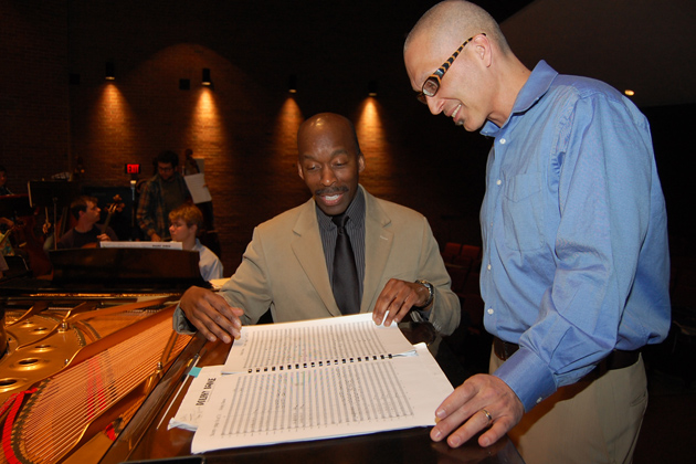 Harvey Felder, left, associate professor of music and director of orchestral studies, and Earl MacDonald, director of jazz studies, review the score for Dolphy Dance. (Ken Best/UConn Photo)