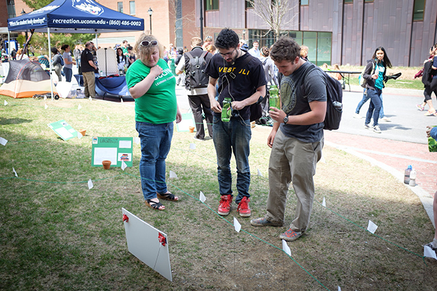 "Sophie Marking '16 (CLAS), left, helps Thomas Chadwick '17 (CLAS) and Paul Ference '17 (ENG) determine their carbon ""pawprint"" as they navigate a maze during the UConn Earth Day Spring Fling held along Fairfield Way on April 22, 2014. (Peter Morenus/UConn Photo)"