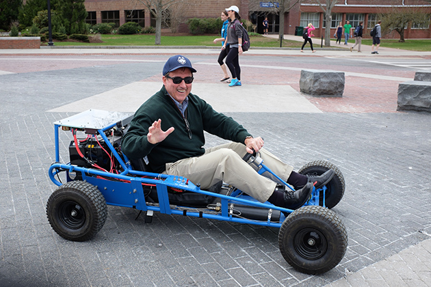 Rich Miller, director of the Office of Environmental Policy, tries out the C2E2 fuel cell-powered go-kart. The Office of Environmental Policy, the Department of Dining Services' Local Routes Program, EcoHusky Student Group, and EcoHouse Learning Community are co-sponsors of the festival held each year on Earth Day. (Peter Morenus/UConn Photo)
