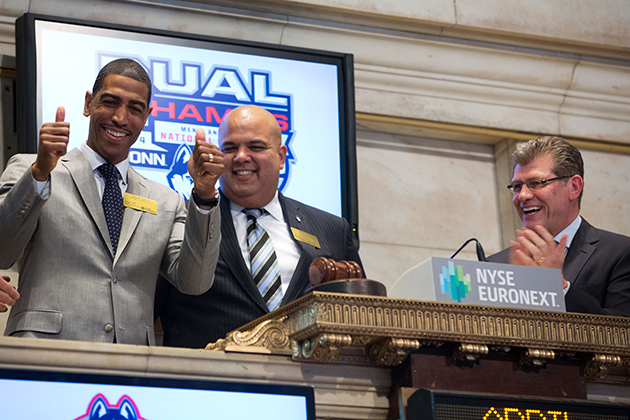 UConn NCAA men's and women's championship coaches Kevin Ollie, left, and Geno Auriemma, right, ring the Closing Bell at The New York Stock Exchange on April 10, accompanied by athletics director Warde Manuel. (Photo by Dario Cantatore/NYSE Euronext)