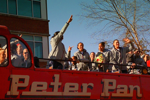 The women's basketball team greets the fans from the bus during a victory lap of campus on April 9. (Angie Reyes/UConn Photo)