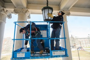 University electricians David Gawlak and Joesph Landry install blue lamps at the Wilbur Cross Building to raise awareness of autism. (Peter Morenus/UConn Photo)