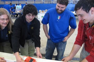 The team from Wolcott Technical High School in Torrington and their mentor, GK-12 Fellow Joe Parisi (center) find success with their modified boat. (William Weir/UConn Photo)