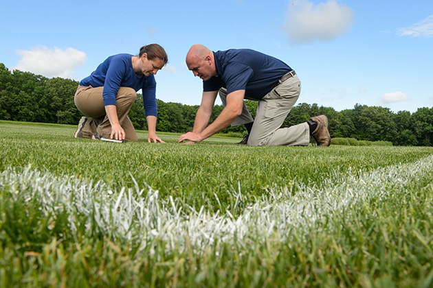Jason Henderson, associate professor of plant science and landscape architecture, and Ph.D. student Julie Campbell, check a plot of turf for crabgrass and weeds on June 6, 2014. (Peter Morenus/UConn Photo)