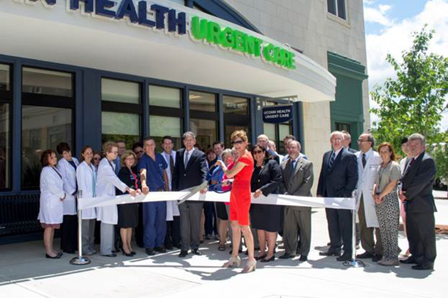 UConn officials, clinical staff, and elected officials join UConn President Susan Herbst (center) and Dr. Frank Torti, UConn Health executive vice president for health affairs (to Herbst's right), for a ribbon cutting to mark the presence of UConn Health medical, dental, and urgent care services in Storrs Center. (UConn Health Photo)