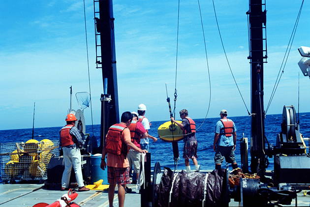 Members of UConn's Underwater Sensor Network and the U.S. Naval Research Lab a sensor node from the back of the research vessel during a test in the Atlantic Sea in 2010. (Zheng Peng/UConn Photo)