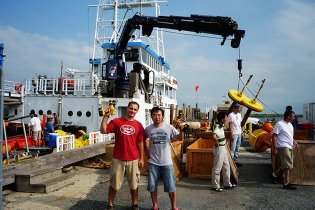 Members of UConn's Underwater Sensor Network and the U.S. Naval Research Lab move the sensor nodes from the deck of the research vessel to their storage boxes. Zheng Peng (foreground right) assistant research professor of computer science and engineering, stands next to Thomas Burchfield, then with the NRL. Behind them are Shengli Zhou, professor of electrical and computer engineering (third from right), and Jeffrey Schindall of NRL (far right). (Zheng Peng/UConn Photo)